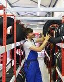 Εργαζόμενοι σε μια αποθήκη εμπορευμάτων με τα ελαστικά αυτοκινήτου για την αλλαγή του αυτοκινήτου Στοκ εικόνες με δικαίωμα ελεύθερης χρήσης