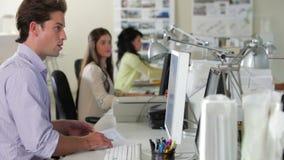 Εργαζόμενοι στα γραφεία στο απασχολημένο δημιουργικό γραφείο απόθεμα βίντεο