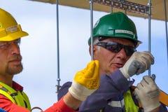 Εργαζόμενοι στα κράνη στο εργοτάξιο οικοδομής Οικοδομές Στοκ Εικόνες