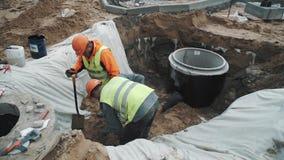 Εργαζόμενοι στα σκληρά καπέλα με τα φτυάρια που σκάβουν την άμμο στην τάφρο υπονόμων στο εργοτάξιο απόθεμα βίντεο