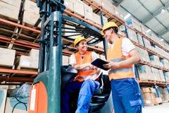 Εργαζόμενοι στην αποθήκη εμπορευμάτων διοικητικών μεριμνών forklift που ελέγχουν τον κατάλογο στοκ εικόνες