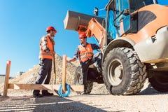 Εργαζόμενοι στο εργοτάξιο οικοδομής που συζητούν τη χρήση των εργαλείων Στοκ Εικόνα