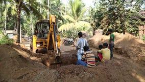 Εργαζόμενοι στο σκάβοντας χώμα βυθοκόρων προσοχής εργοτάξιων οικοδομής απόθεμα βίντεο