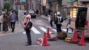 Εργαζόμενοι συντήρησης στην οδό που επισκευάζει την υποδομή Τακτοποιώντας κυκλοφορία φιλμ μικρού μήκους