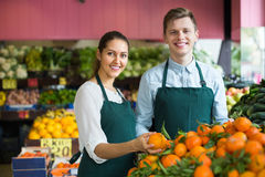 Εργαζόμενοι υπεραγορών που πωλούν τα πορτοκάλια Στοκ Εικόνες