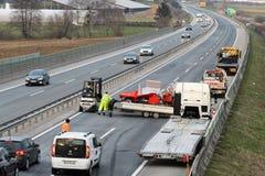 Εργαζόμενοι φορτηγών ρυμούλκησης που καθαρίζουν τα συντρίμμια από το τροχαίο ατύχημα στην εθνική οδό, απάντηση υπηρεσιών επειγόντ Στοκ Φωτογραφία
