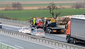 Εργαζόμενοι φορτηγών ρυμούλκησης που καθαρίζουν τα συντρίμμια από το τροχαίο ατύχημα στην εθνική οδό, απάντηση υπηρεσιών επειγόντ Στοκ Εικόνα