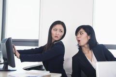Εργαζόμενος ανώτερων υπαλλήλων που κρύβει τον υπολογιστή της από το συνάδελφο Στοκ εικόνες με δικαίωμα ελεύθερης χρήσης