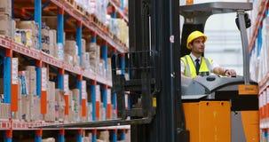 Εργαζόμενος αποθηκών εμπορευμάτων αρσενικών που χρησιμοποιεί forklift το φορτηγό απόθεμα βίντεο