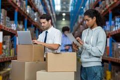 Εργαζόμενος αποθηκών εμπορευμάτων που εργάζεται στο lap-top και την ψηφιακή ταμπλέτα στοκ εικόνες με δικαίωμα ελεύθερης χρήσης
