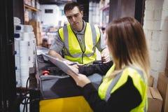 Εργαζόμενος αποθηκών εμπορευμάτων που μιλά με forklift τον οδηγό στοκ εικόνα