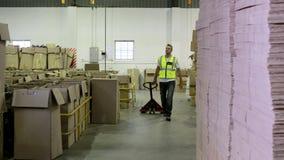Εργαζόμενος αποθηκών εμπορευμάτων που τραβά το καροτσάκι στη κάμερα απόθεμα βίντεο