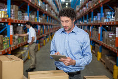Εργαζόμενος αποθηκών εμπορευμάτων που χρησιμοποιεί την ψηφιακή ταμπλέτα στοκ εικόνα
