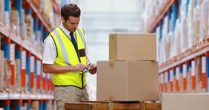 Εργαζόμενος αποθηκών εμπορευμάτων που χρησιμοποιεί την ψηφιακή ταμπλέτα ελέγχοντας τις συσκευασίες φιλμ μικρού μήκους