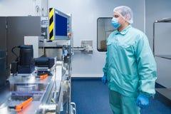 Εργαζόμενος ατόμων εργοστασίων βιομηχανίας φαρμακείων στη προστατευτική ενδυμασία στις αποστειρωμένες συνθήκες εργασίας που λειτο στοκ εικόνα με δικαίωμα ελεύθερης χρήσης