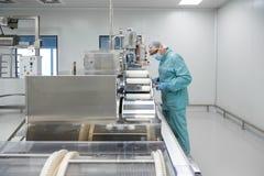 Εργαζόμενος ατόμων εργοστασίων βιομηχανίας φαρμακείων στη προστατευτική ενδυμασία στις αποστειρωμένες συνθήκες εργασίας που λειτο στοκ εικόνες