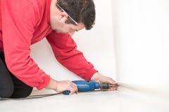Εργαζόμενος ατόμων στο κόκκινο πουκάμισο που γονατίζει στο πάτωμα που τρυπά μια τρύπα με τρυπάνι Στοκ Εικόνες