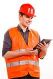 Εργαζόμενος ατόμων στο σκληρό καπέλο φανέλλων ασφάλειας που χρησιμοποιεί την ταμπλέτα Στοκ φωτογραφία με δικαίωμα ελεύθερης χρήσης