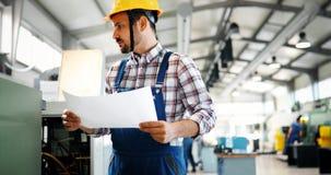 Εργαζόμενος βιομηχανίας που εισάγει τα στοιχεία CNC στη μηχανή στο εργοστάσιο στοκ εικόνα με δικαίωμα ελεύθερης χρήσης