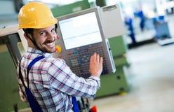 Εργαζόμενος βιομηχανίας που εισάγει τα στοιχεία CNC στη μηχανή στο εργοστάσιο Στοκ Φωτογραφία