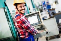 Εργαζόμενος βιομηχανίας που εισάγει τα στοιχεία CNC στη μηχανή στο εργοστάσιο Στοκ Εικόνα
