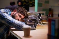 Εργαζόμενος γραφείων αρσενικών κοιμισμένος στο γραφείο που λειτουργεί αργά στο lap-top στοκ φωτογραφίες