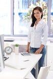 Εργαζόμενος γραφείων θηλυκών που υπερασπίζεται το χαμόγελο γραφείων Στοκ Εικόνες