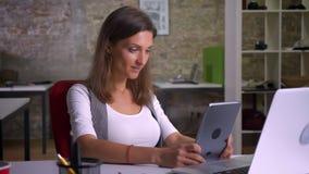 Εργαζόμενος γραφείων θηλυκών Attractiver που κοιτάζει βιαστικά στην ταμπλέτα που χαμογελά στον εργασιακό χώρο στο εσωτερικό απόθεμα βίντεο