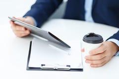 Εργαζόμενος γραφείων με την ταμπλέτα και papercup του καφέ Στοκ Εικόνες
