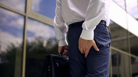 Εργαζόμενος γραφείων που αισθάνεται τον πόνο hemorrhoid περπατώντας, στατικός τρόπος ζωής, υγεία στοκ εικόνα