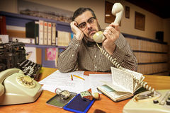 Εργαζόμενος γραφείων που εκπλήσσεται με το τηλέφωνο διαθέσιμο στο γραφείο Στοκ Εικόνες