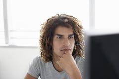 Εργαζόμενος γραφείων που εξετάζει το όργανο ελέγχου υπολογιστών Στοκ Φωτογραφίες