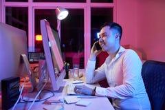 Εργαζόμενος γραφείων που εργάζεται στο γραφείο μέχρι αργά το βράδυ στοκ εικόνα