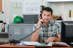 Εργαζόμενος γραφείων στο τηλέφωνο στον πελάτη Στοκ εικόνα με δικαίωμα ελεύθερης χρήσης