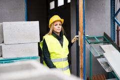 Εργαζόμενος γυναικών που στέκεται σε μια βιομηχανική περιοχή Στοκ εικόνα με δικαίωμα ελεύθερης χρήσης