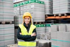 Εργαζόμενος γυναικών που στέκεται σε μια βιομηχανική περιοχή Στοκ φωτογραφία με δικαίωμα ελεύθερης χρήσης