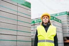Εργαζόμενος γυναικών που στέκεται σε μια βιομηχανική περιοχή Στοκ φωτογραφίες με δικαίωμα ελεύθερης χρήσης