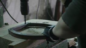 Εργαζόμενος γυναικών που χρησιμοποιεί μια διάτρηση για να κάνει τις τρύπες σε ένα κομμάτι του μετάλλου στο diy εργαστήριό της - απόθεμα βίντεο
