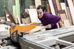 Εργαζόμενος γυναικών που χρησιμοποιεί τη μηχανή πριονιών για να κάνει τα έπιπλα Στοκ Εικόνες