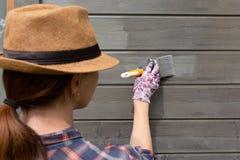 Εργαζόμενος γυναικών που χρωματίζει τον ξύλινο εξωτερικό τοίχο σπιτιών με το πινέλο και το ξύλινο προστατευτικό χρώμα στοκ εικόνες