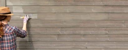 Εργαζόμενος γυναικών που χρωματίζει τον ξύλινο εξωτερικό τοίχο σπιτιών με το πινέλο και το ξύλινο προστατευτικό χρώμα στοκ εικόνα με δικαίωμα ελεύθερης χρήσης