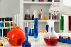 Εργαζόμενος εργαστηρίων που παίρνει το δείγμα του κόκκινου υγρού από τη φιάλη στον πίνακα στοκ εικόνα με δικαίωμα ελεύθερης χρήσης