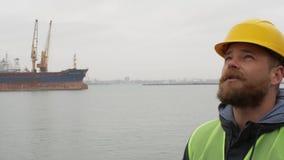 Εργαζόμενος θαλάσσιων λιμένων με μια γενειάδα και ένα κράνος στο υπόβαθρο των σκαφών φιλμ μικρού μήκους