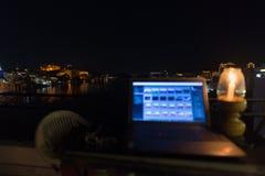 Εργαζόμενος διακινούμενος, έννοια των ψηφιακών νομάδων Lap-top στον πίνακα με τη φυσική πανοραμική άποψη τή νύχτα Εστίαση στην αν Στοκ Εικόνα