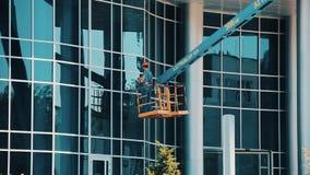 Εργαζόμενος καθαριστής γυαλιού ατόμων σε ένα υδραυλικό καθαρίζοντας παράθυρο ανελκυστήρων απόθεμα βίντεο