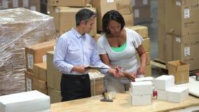 Εργαζόμενος και διευθυντής που ελέγχουν τα αγαθά πριν από την αποστολή απόθεμα βίντεο