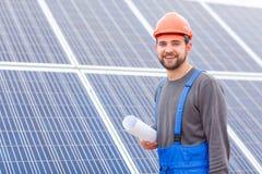Εργαζόμενος με ένα έγγραφο στο χέρι του και ένα κράνος στο κεφάλι του σε ένα κλίμα των ηλιακών πλαισίων Στοκ εικόνες με δικαίωμα ελεύθερης χρήσης