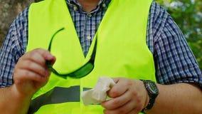 Εργαζόμενος με τα καθαρίζοντας γυαλιά ηλίου 4 πετσετών φιλμ μικρού μήκους