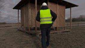 Εργαζόμενος με τα καρφιά και σφυρί που περπατά στο ξύλινο κτήριο απόθεμα βίντεο