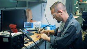 Εργαζόμενος με τα προσθετικά χέρια που συγκολλούν ένα κύκλωμα σε ένα εργαστήριο απόθεμα βίντεο